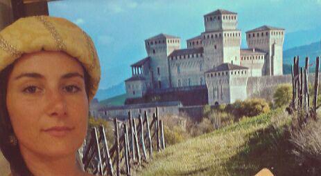 Ritratto di Emanuela, guida turistica abilitata con il castello di Torrechiara